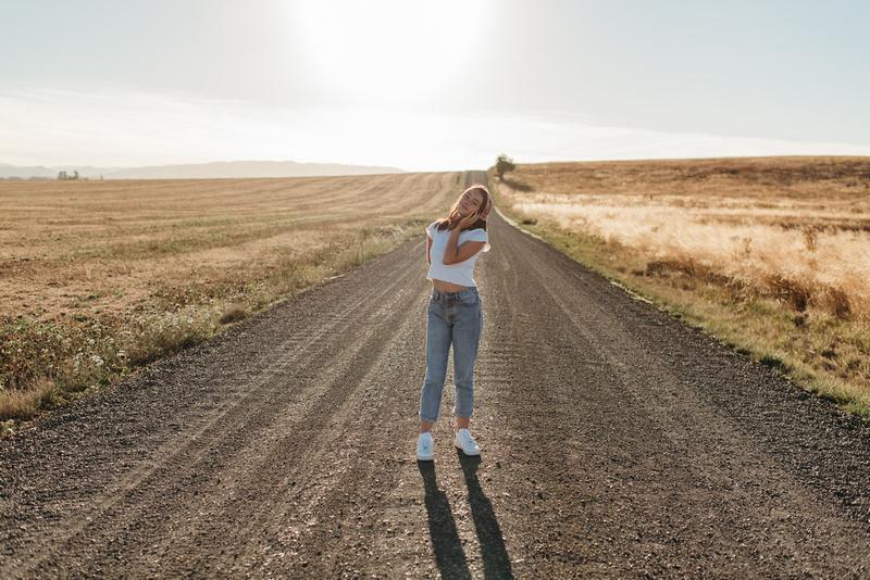 High school senior standing on a dirt road