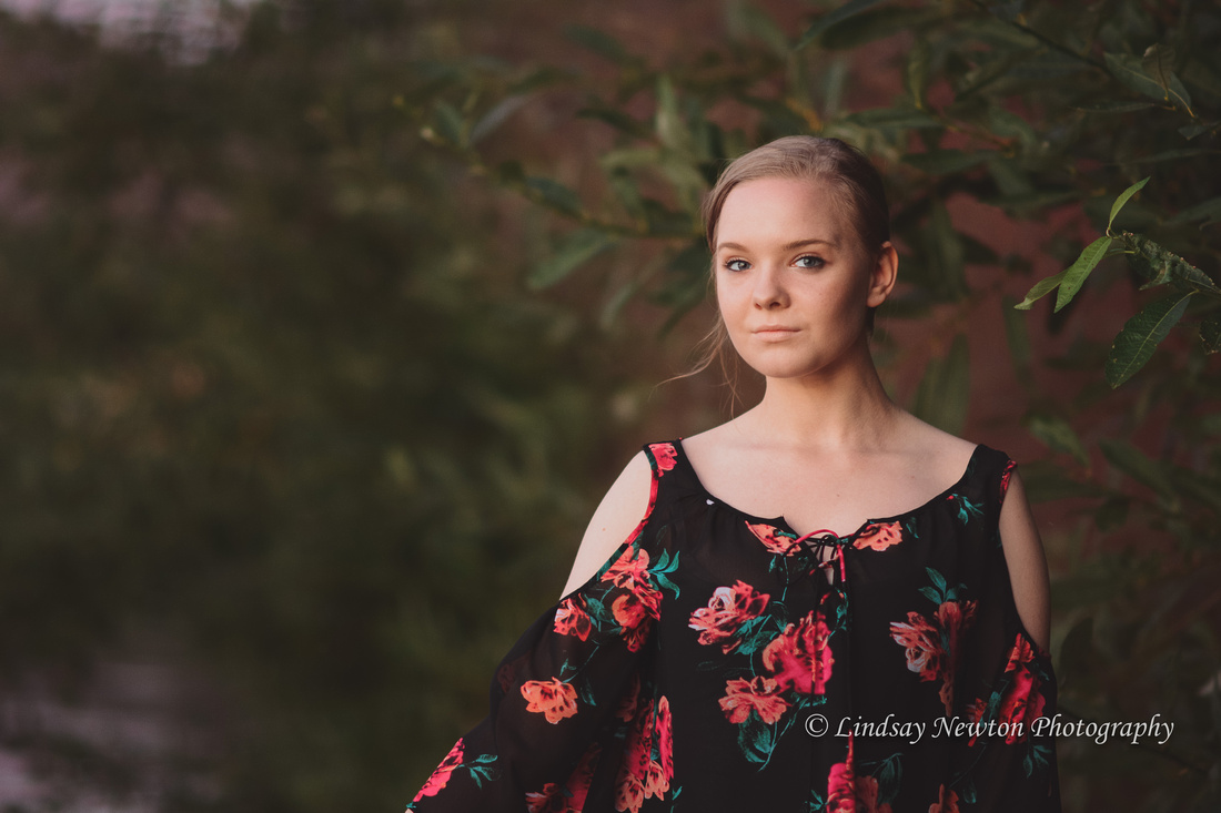 Senior Girl photo session with subtle red smoke bomb in trees
