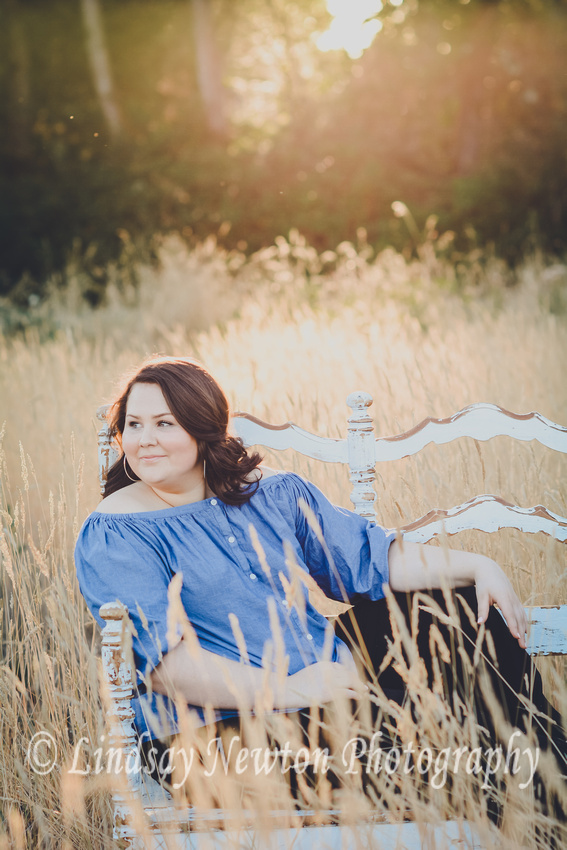 Senior girl sitting in a wheat field in the golden summer sun at Minto Brown Park in Salem, Oregon
