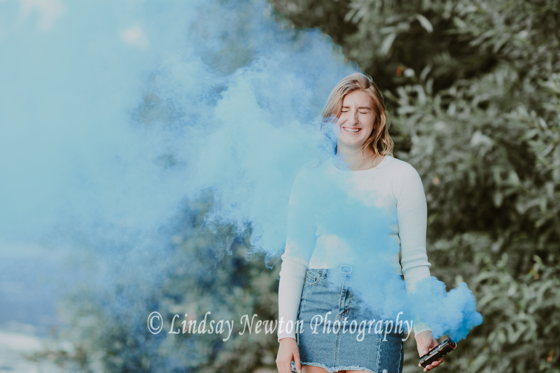 Funny senior girl photo session with a blue smoke bomb