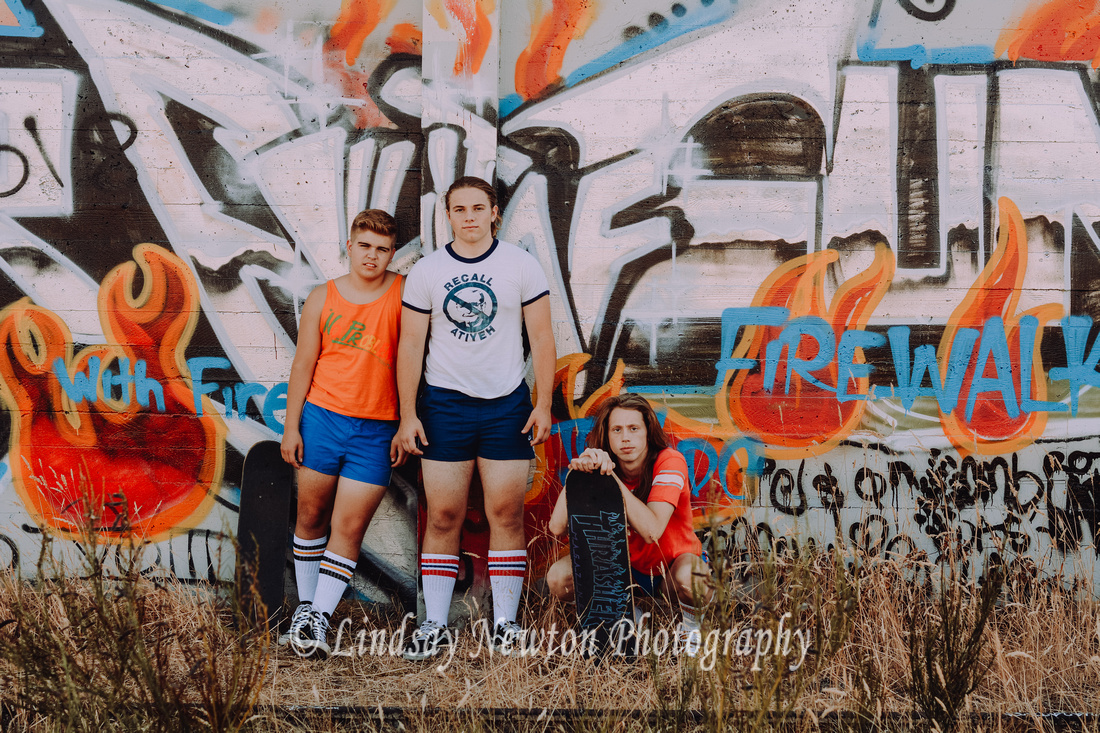 70's themed guys senior session in short shorts with skateboards and graffiti in Portland, Oregon.