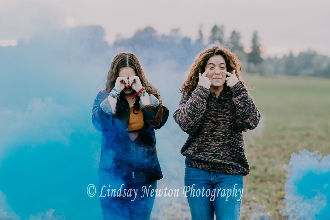 Funny senior girl photo session with blue smoke bomb