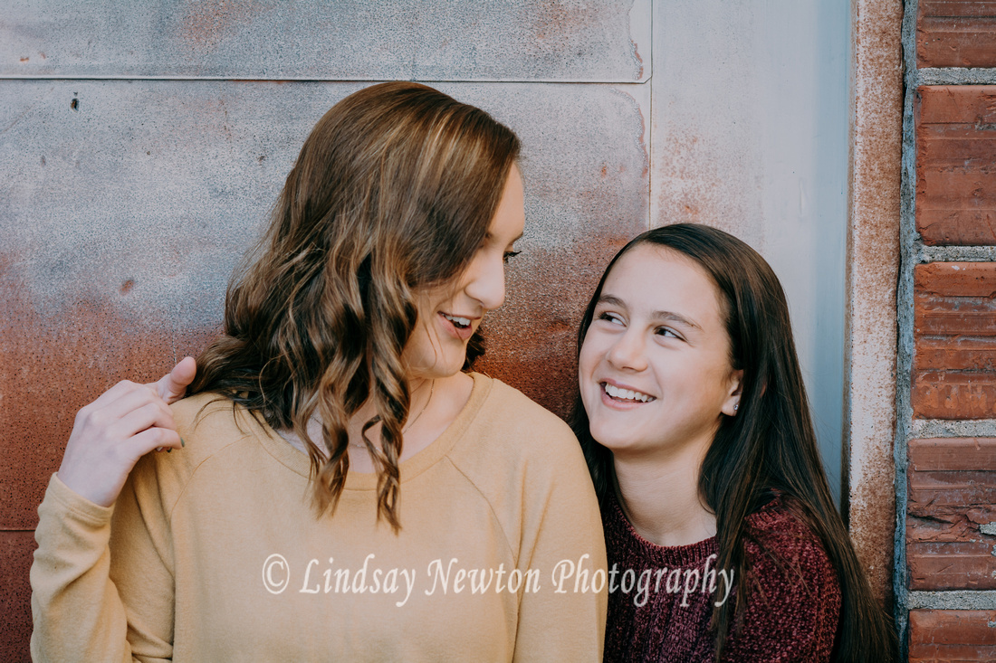 Sisters laughing with each other during a family photo session in downtown Salem, Oregon.