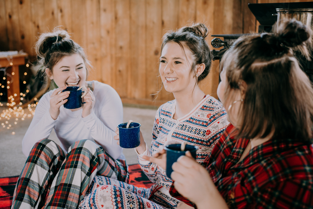 Senior girl friend session in pajamas with hot cocoa at a cabin