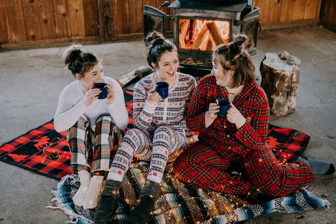 Senior friend pajama session at a cabin with hot cocoa