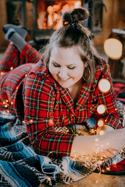 Senior girl pajama session with a cozy fire in a cabin.