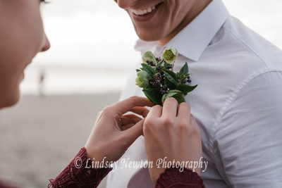 pinning the boutonniere on during a styled shoot on the Washington coast.
