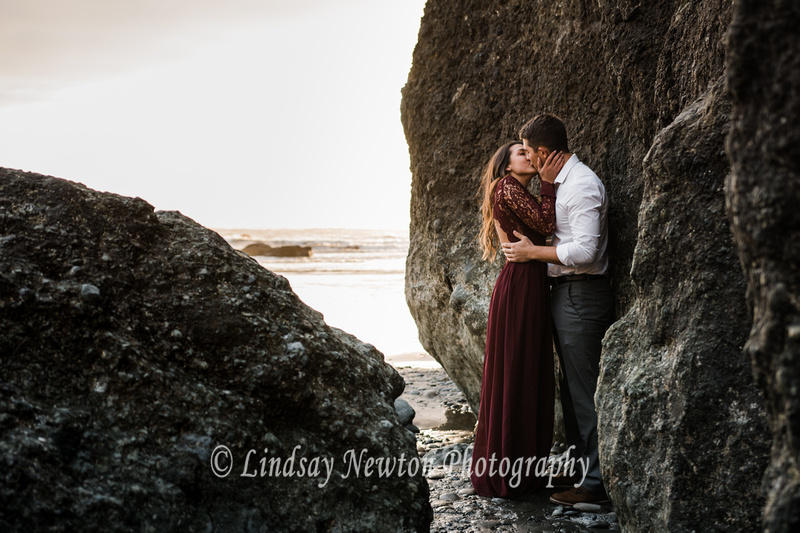 Recently engaged couple kissing by the ocean at Ruby Beach in Washington