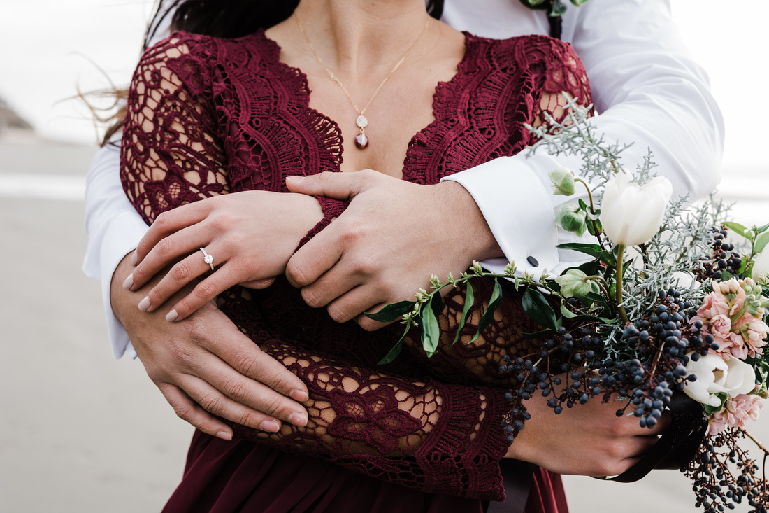 Engaged couple in an embrace, showcasing her ring.