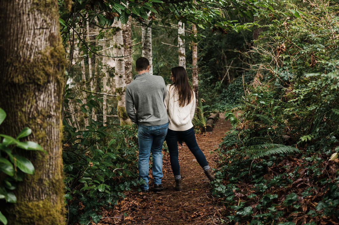Engaged couple walking down the trail in the woods.