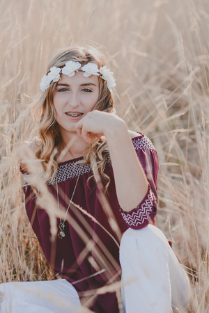 Senior girl with flower crown sitting in a wheat field in Salem, Oregon