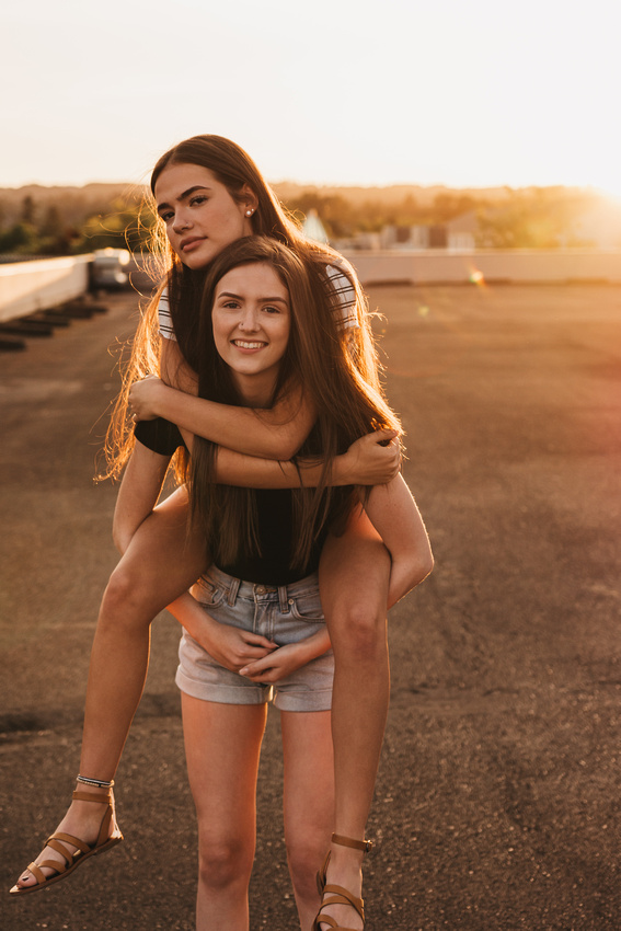 Best friends on a rooftop at sunset