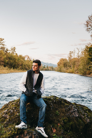 Senior guy posing with his Jeep on the Santiam River in the fall.