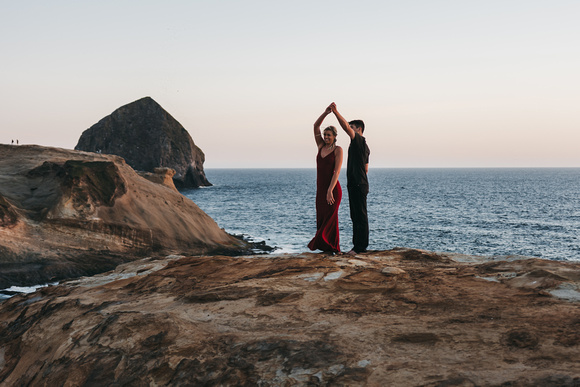 Engagement session on the Oregon Coast. Couple is dancing in front of haystack rock as the sun sets.