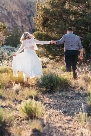 Engagement session at Smith Rock, Oregon. Couple running away in the sage brush.