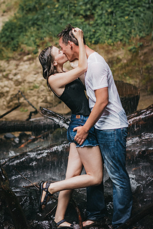 Engagement session at Shellburg Falls in Oregon. Couple kissing under the waterfall.