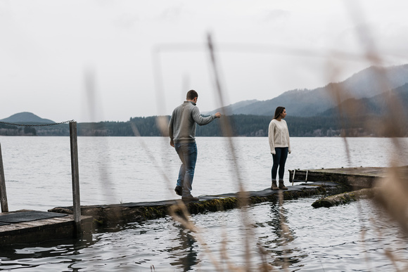 Engagement photos at Lake Quinault. Couple walking out on a dock on the lake.