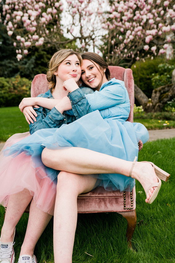 High School Senior Best Friends sitting on a pink chair in front of a tulip tree in the spring.