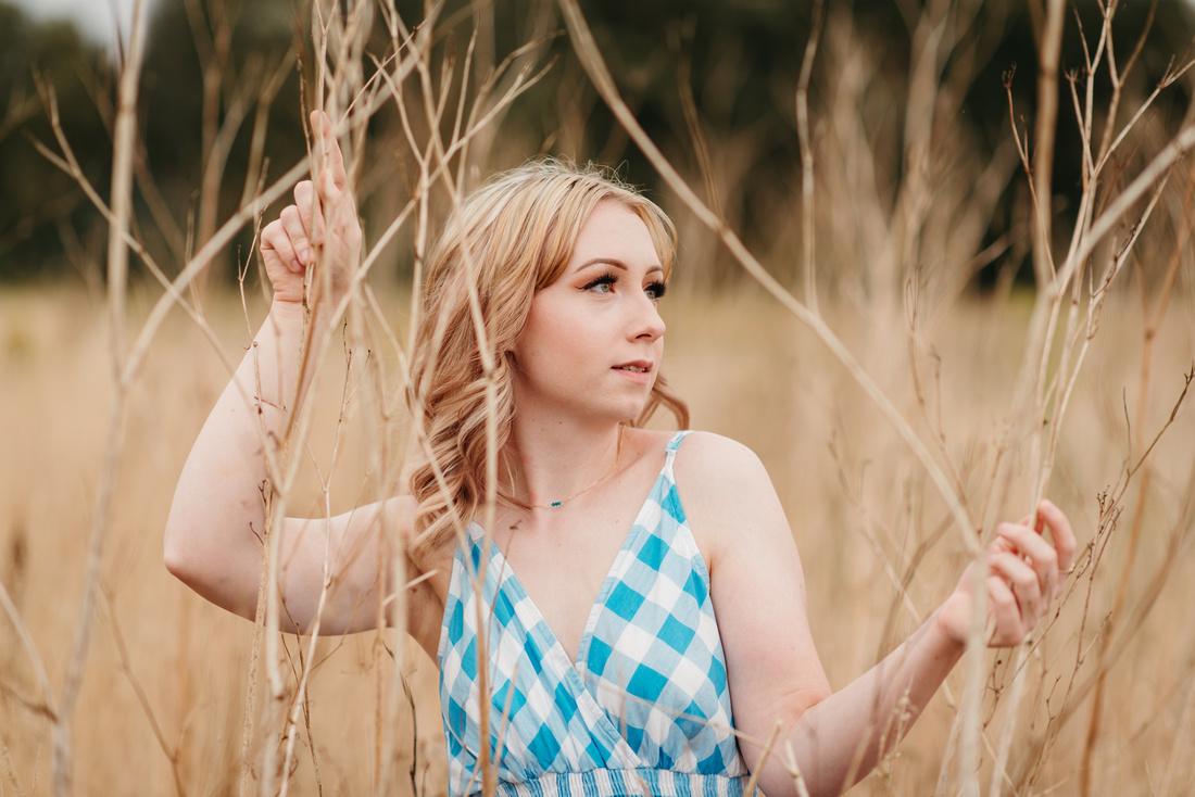 High school senior girl posing in a field.