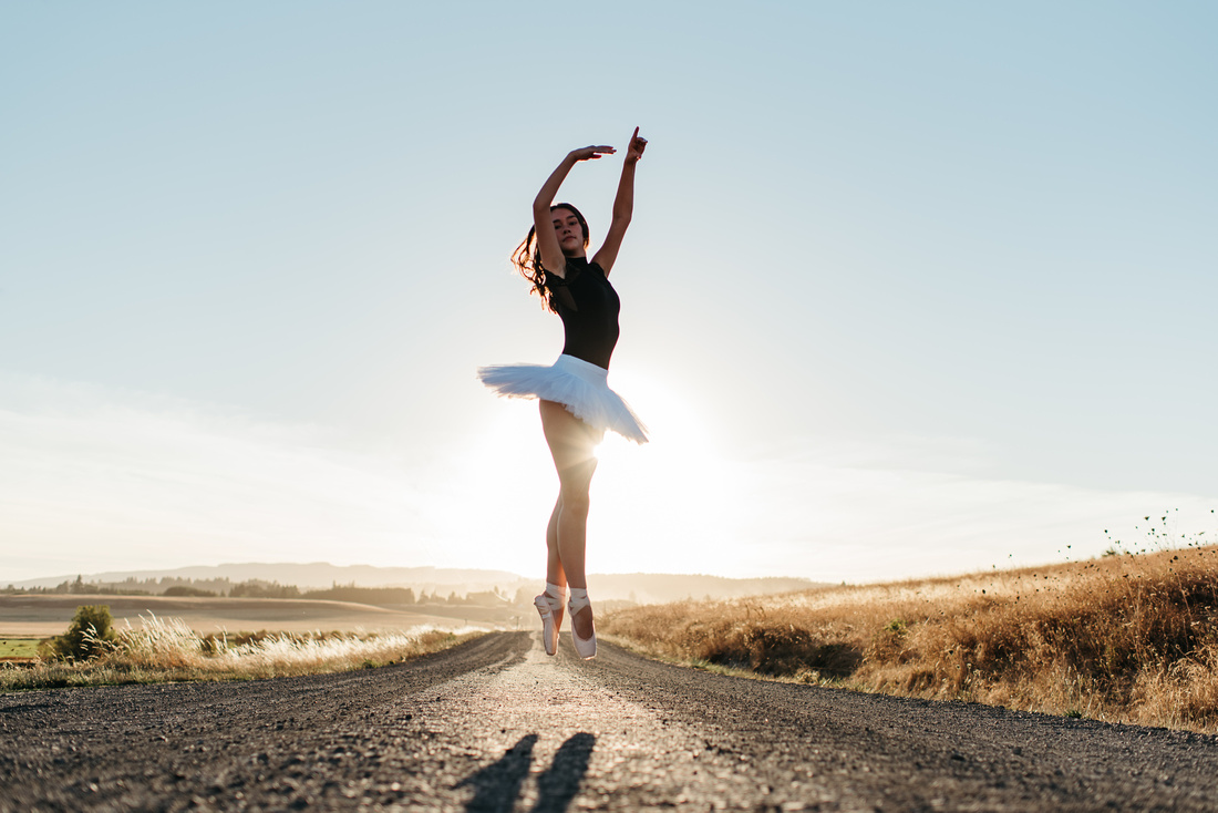 High School Ballerina on a dirt road with the sun shining behind her.