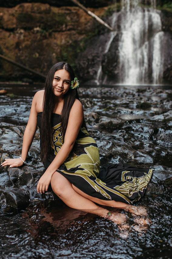 High school senior girl sitting in front of a waterfall.