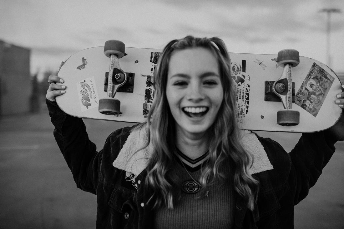High school senior holding skateboard behind her head.