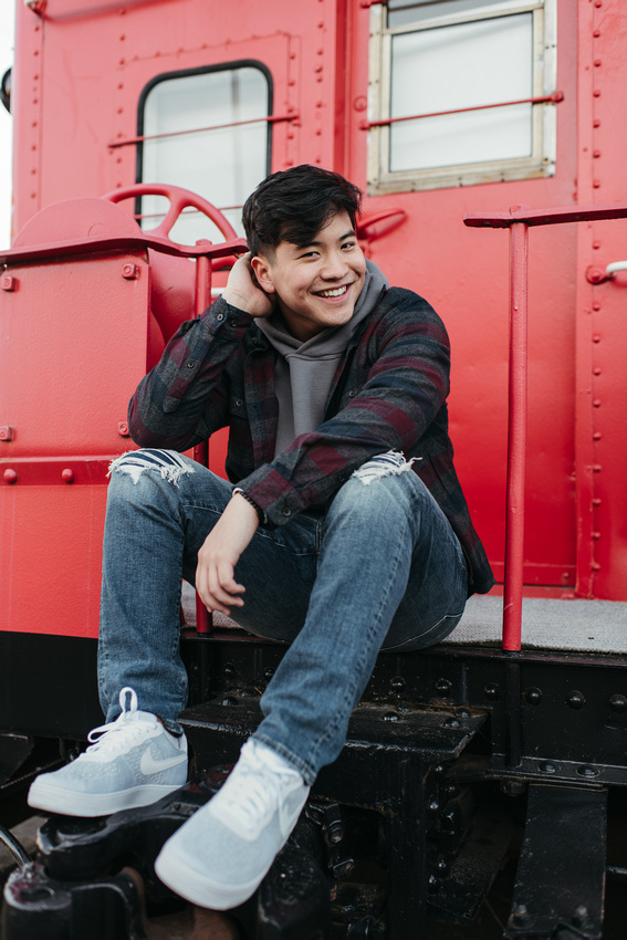 High school senior guy sitting on the back of a train caboose.