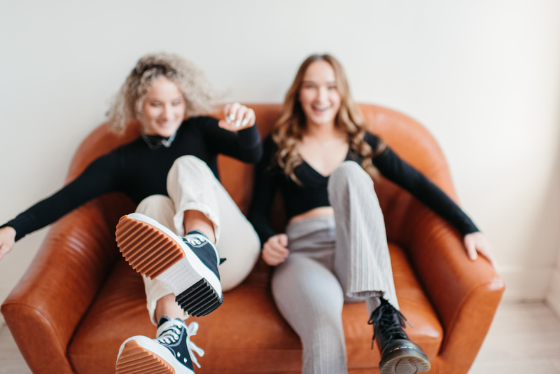 high school senior girls jumping onto a couch at the Gray Lab in Salem, Oregon.